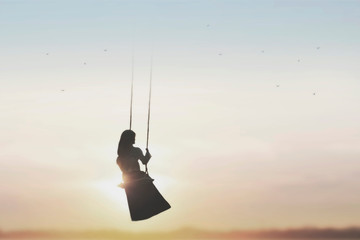 free woman on the swing taking a breath in the sky