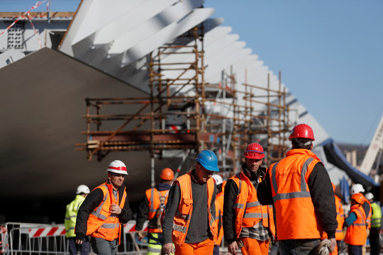 Builders are pictured at the construction site of the new Genoa bridge, also known as the Polcevera viaduct