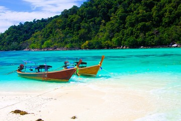 View on secluded beach in remote bay with turquoise water and thai long-tail boats, Ko Lipe, Thailand