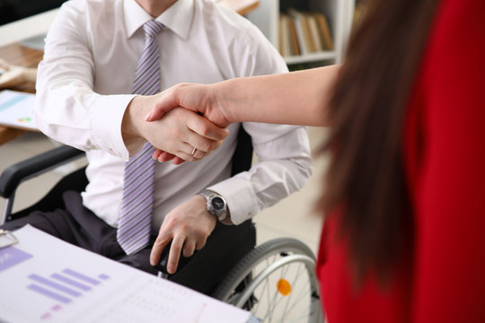 Disabled man in a shirt and tie shakes hands with his new boss who hired him closeup. Adaptation of people with disabilities in a society concept