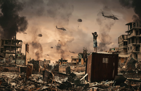 Homeless little boy watching Helicopters and soldiers in sky in destroyed and bombarded city between smoke.