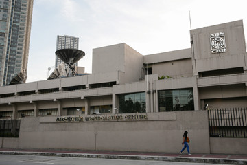 A woman walks outside the ABS-CBN Broadcasting Center, the office of the country's top broadcast network, following a move by the Philippine government to scrap its franchises, in Quezon City