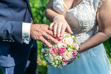 hands groom and bride with wedding rings and wedding bouquet flowers celebration love symbol