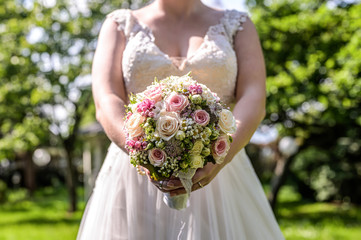 Wedding bouquet of flowers held by bride closeup. Pink and yellow roses flowers