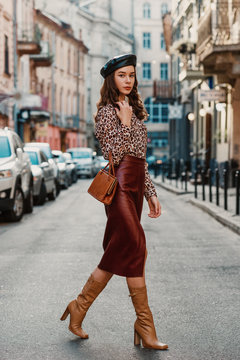 Outdoor full body fashion portrait of elegant luxury woman wearing leopard print blouse, faux leather dark red skirt, beret, holding small brown classic handbag, walking in street of European city