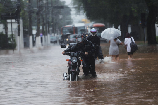 A man pushes a motorcycle through a flooded street after heavy rains in Butanta neighbourhood in Sao Paulo