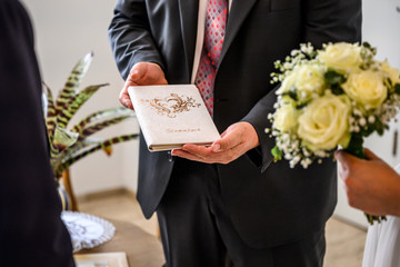 minister hoding family book written in german stammbuch in front of Wedding flowers held by bride closeup. yellow roses