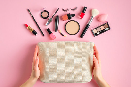 Female hands holding makeup bag with cosmetic beauty products over pink background. Flat lay, top view