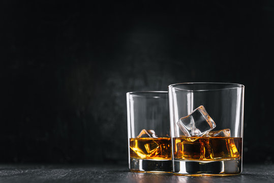 two glasses of alcoholic drink on a dark background