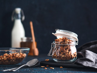 Homemade granola in glass jar on dark table. Ingredients for healthy breakfast - granola, milk and honey. Copy space for text. Low key.