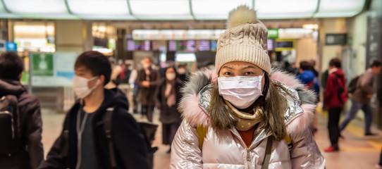 Traveler woman wears medical mask to protect against coronavirus on public transport station.