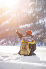 Outdoor adventure: Caucasian girl is sitting in the snow and enjoying the view. Beautiful winter landscape, Austria