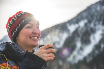 Outdoor wilderness adventure: Caucasian girl is drinking a metal cup of tea