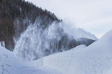 Removing the snow with a snow blower in winter
