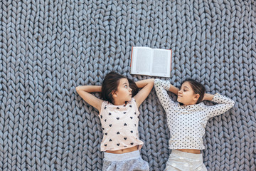 Children lying down and relaxing with a book on chunky giant woolen blanket