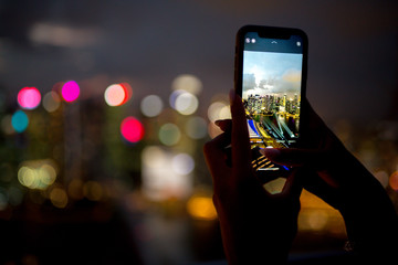 A girl takes pictures of the night city from a skyscraper in Singapore and Kuala Lumpur on her phone