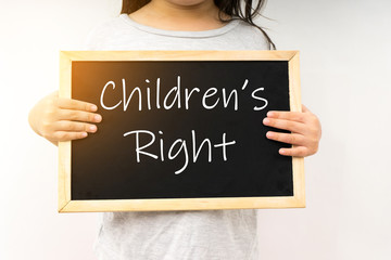 Children's right concept with a young girl hold the chalkboard.