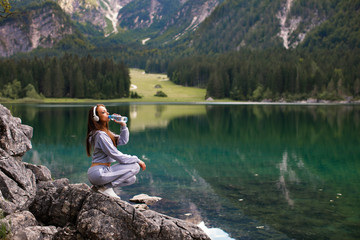 Young sports woman drinks water on a mountain next to the lake