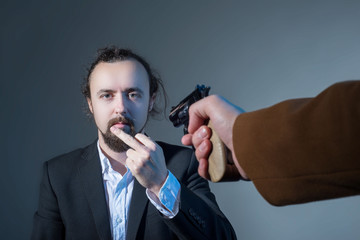 closeup portrait of a man showing his middle finger, whose face is pointing his hand with another mans gun. On a gray background. The concept of killing. Dramatic picture.