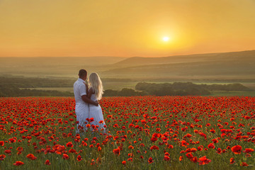 Loving couple hug one another during romantic date in marvellous spring poppy field with bright sunset above forest and mountains. People in wild nature horizontal background.
