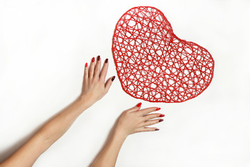 Hands at a red heart on a white background.Nail design on long square nails from light red to dark color of nail Polish.