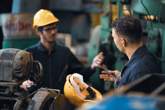 Scene shot of 2 industrial workers arguing planning, the procedure of work in the factory with selective focus, concept industrial workers process, manufacturing operation, working confliction.