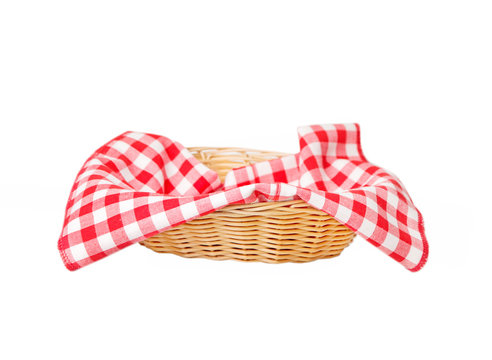 Wicker basket with a red checkered napkin inside isolated on white background
