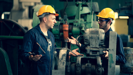 Fototapeta Scene shot of 2 industrial workers feeling upset with the engine machine of the factory, arguing planning, the procedure of work in the factory, concept industrial worker life, working confliction. obraz