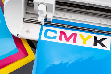 production making CMYK sticker with plotter cutting machine on cyan blue colored vinyl film. Advertising Industry diy design concept background.