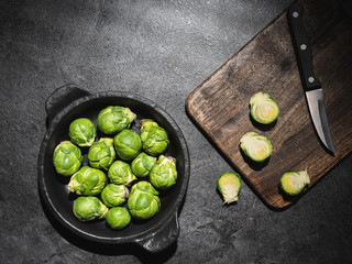 Keuken foto achterwand Brussel Fresh green brussels sprouts in black bowl and cutting board with knife on dark background. Overhead shot.