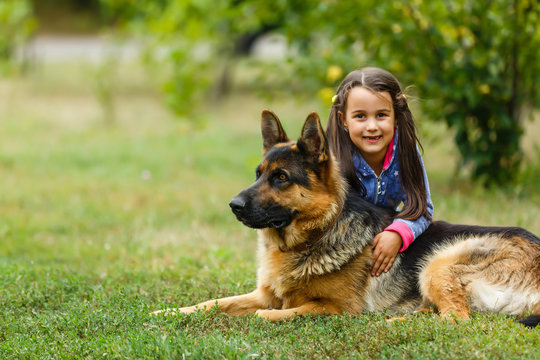 Pretty little girl, Gives a command to sit to german shepherd dog.