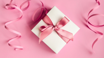 White gift box with pink ribbon on the pink background