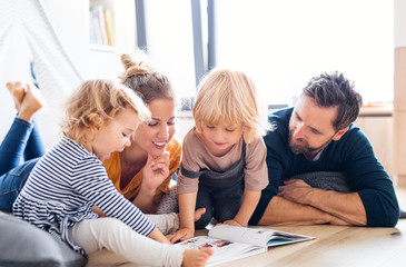 Tuinposter Op straat Young family with two small children indoors in bedroom reading a book.
