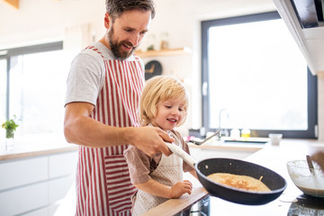 Wall Mural - A side view of small boy with father indoors in kitchen making pancakes.
