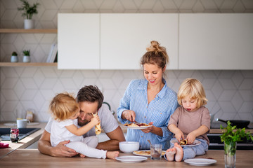 Wall Mural - Young family with two small children indoors in kitchen, eating pancakes.