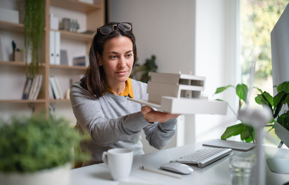 Architect with model of a house sitting at the desk indoors in office.
