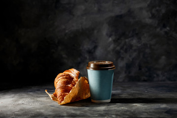 Fresh hot coffee in paper cup and sweet cake on dark mood background.
