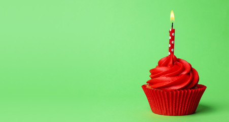 Delicious birthday cupcake with red cream and burning candle on green background. Space for text