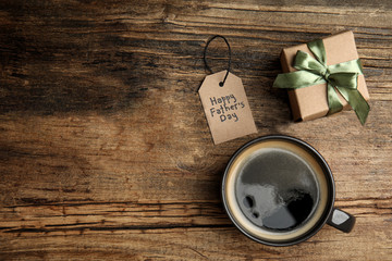 Cup of coffee, gift box and tag with phrase HAPPY FATHER'S DAY on wooden table, flat lay. Space for text