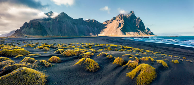 View from flying drone. Stunning autumn scene of Stokksnes cape with Vestrahorn (Batman Mountain) on background. Panoramic Icelandic view of black sand dunes with fresh green grass.