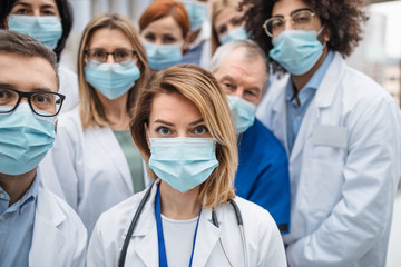 Group of doctors with face masks looking at camera, corona virus concept. Wall mural