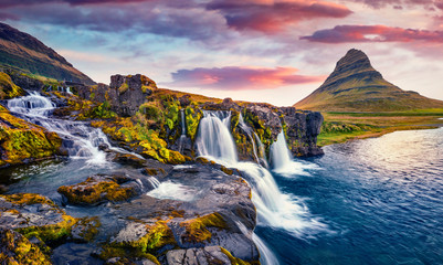 Fotobehang Noord Europa Dramatic morning view of popular tourast destination - Kirkjufellsfoss Waterfall. Colorful sunrise on Snaefellsnes peninsula, Iceland, Europe. Beauty of nature concept background..