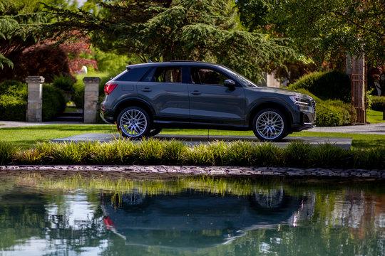 Audi Q2 SUV spiegelt sich in einem Teich in einem Park