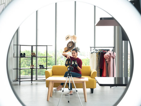 Asian entrepreneur woman show two fashion shoes accessory and record live in camera for upload on social media and channel for promote brand online through selfie circle ring light in living room