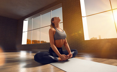 Tuinposter Ontspanning Yoga woman. Young woman doing yoga in loft on sunrise.