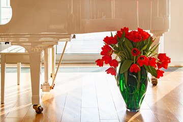 green glass vase with red tulips at the white piano