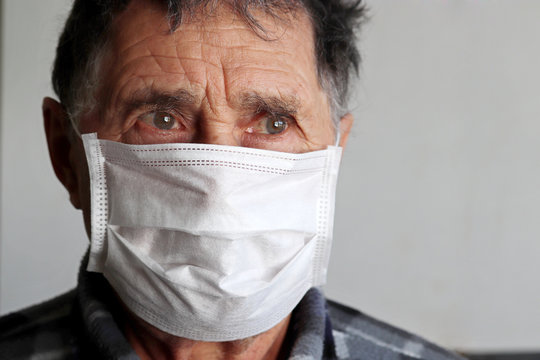 Elderly man in medical mask looks upset. Concept of coronavirus protection, illness, fever, cold and flu
