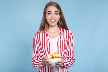 Young beautiful girl with potato chips in bowl on blue background