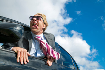 Excited businessman traveling in a car hanging out the window with wind blowing his tie and tongue