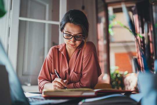 Young concentrated woman in spectacles writing notes in notebook while working in modern office, texting business message communicating online with client feels satisfied successful concept